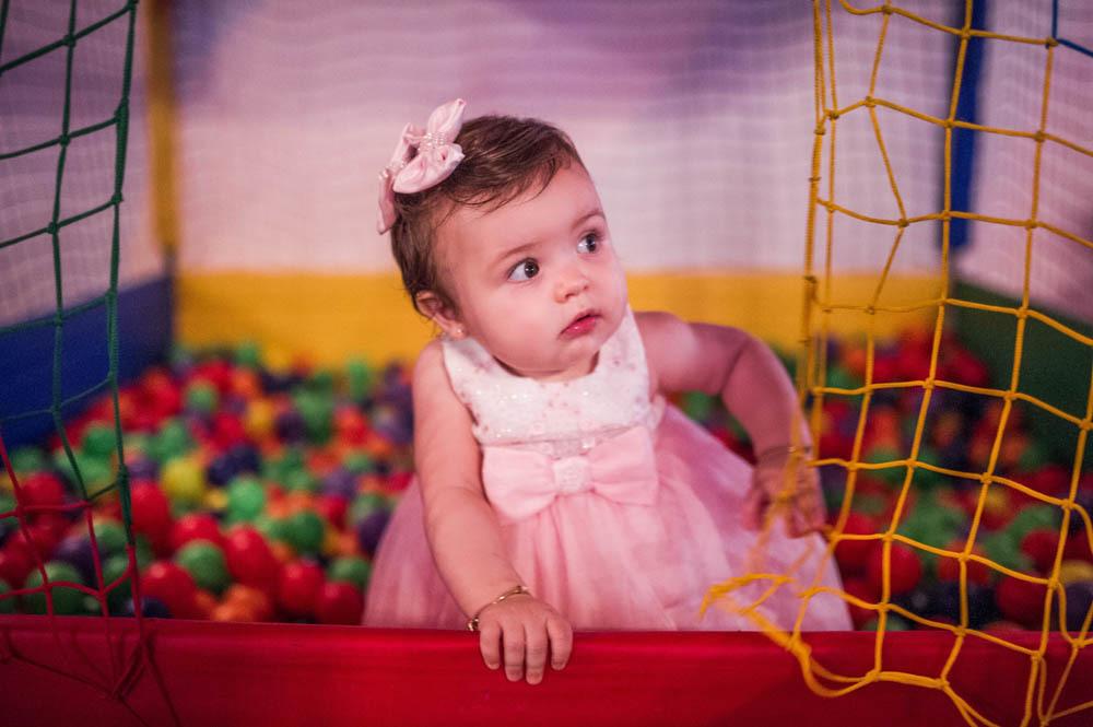 bebê menina brincando em pé olhando para fora na piscina de bolinhas