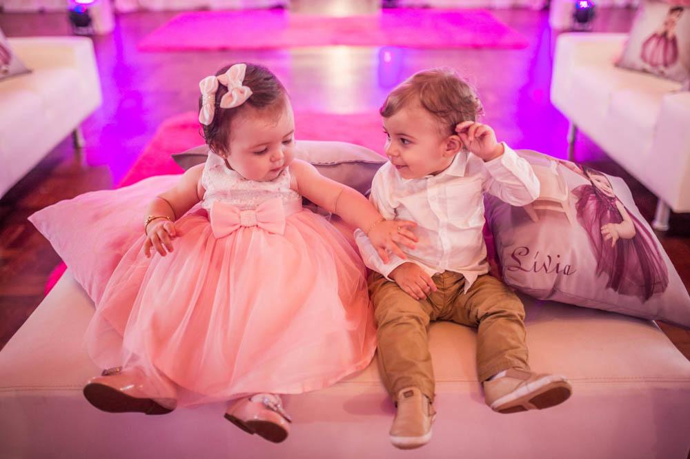 menina sentada dando a mão para um menino sentados em seu aniversário