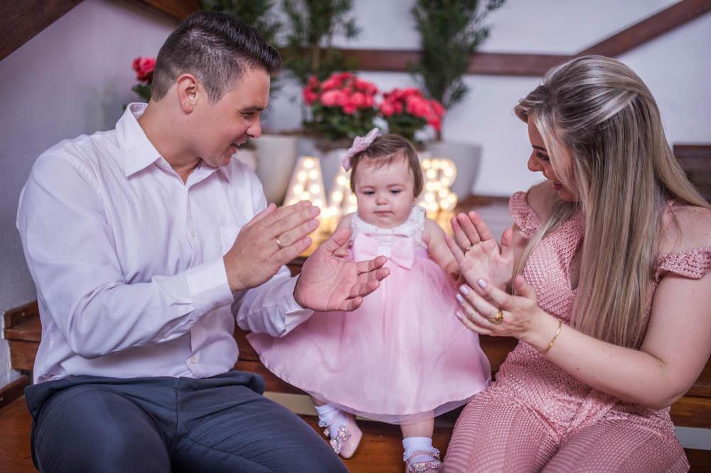 pai e mãe sentados com filha de um ano batendo palmas cantando parabéns