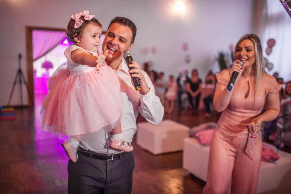 pai e mãe com microfone na mão entrando com a bebê menina no colo e cantando