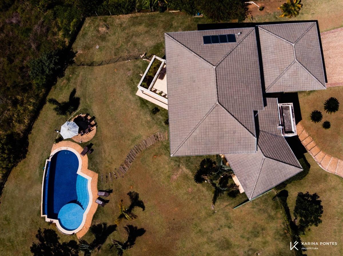 #ParaCegoVer:Fotografia da piscina de borda infinita com a  cobertura da residência LR Quebec  com telhado aparente.