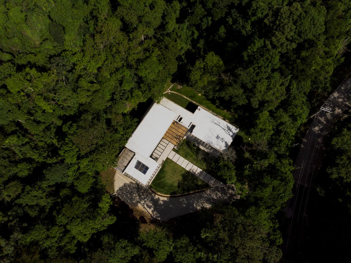 #ParaCegoVer: Fotografia colorida da residência Quebec L vista do alto com a mata no entorno