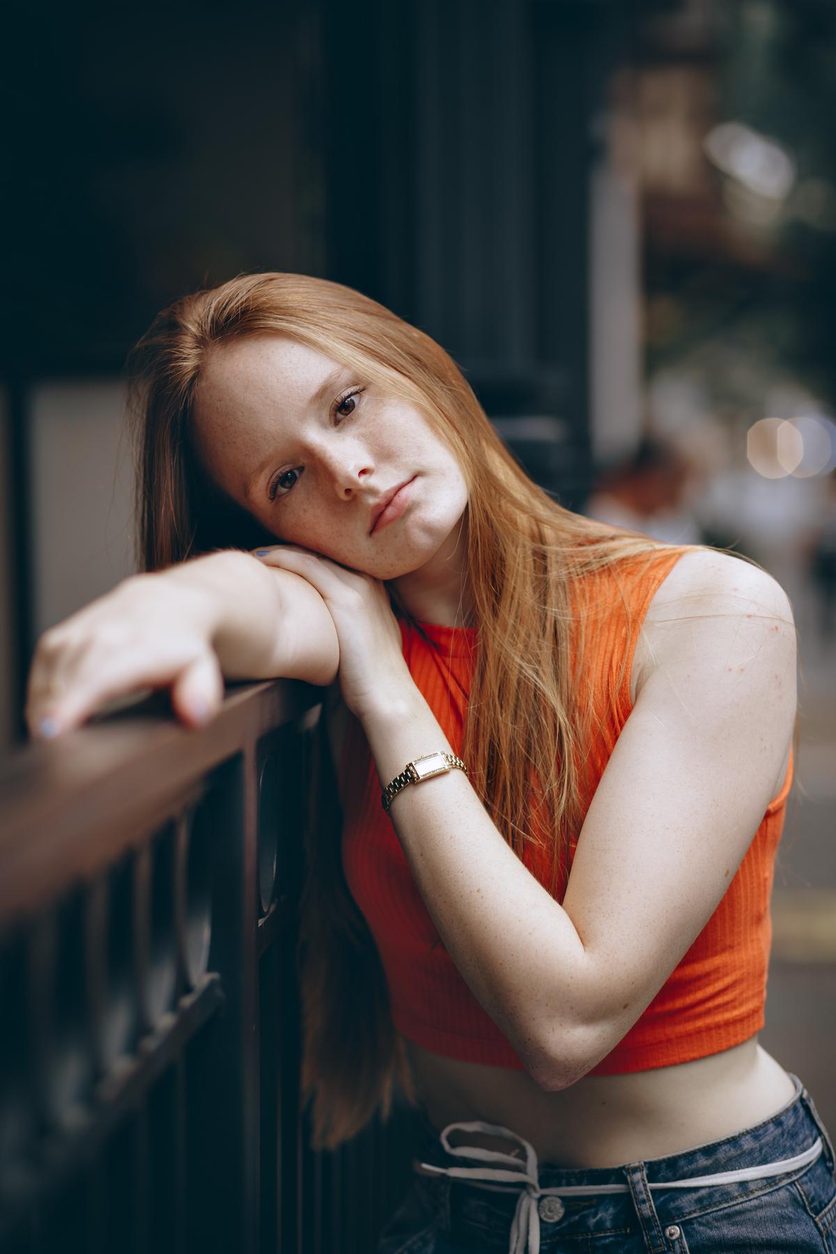 garota olhando com um olhar calmo para a camera em frente a the fifities burguer