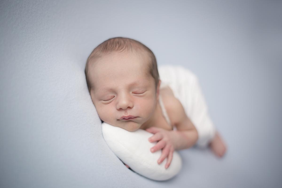 Newborn pose lateral em manta azul, ensaio Brasilia DF