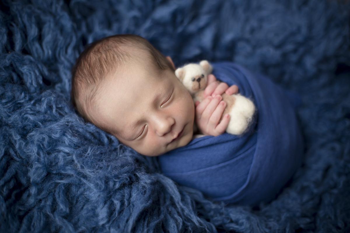 Bebe newborn em flokati azul jens, segurando ursinho em ensaio Newborn em Brasilia