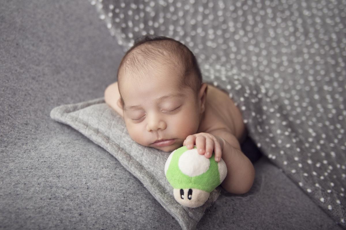 Newborn menino Brasilia, 16 dias, segurando pelucia