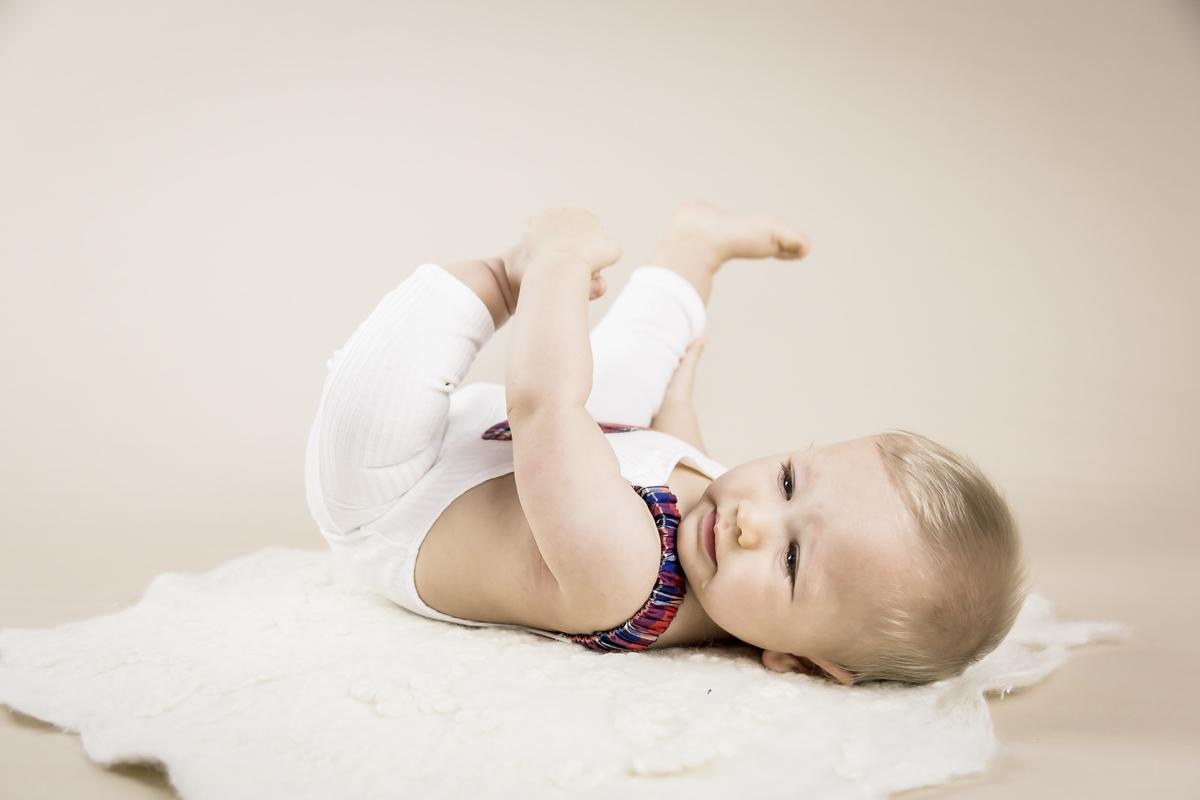 bebe de seis meses, barriguinha pra cima, segundando o pé, acompanhamento primeiro ano