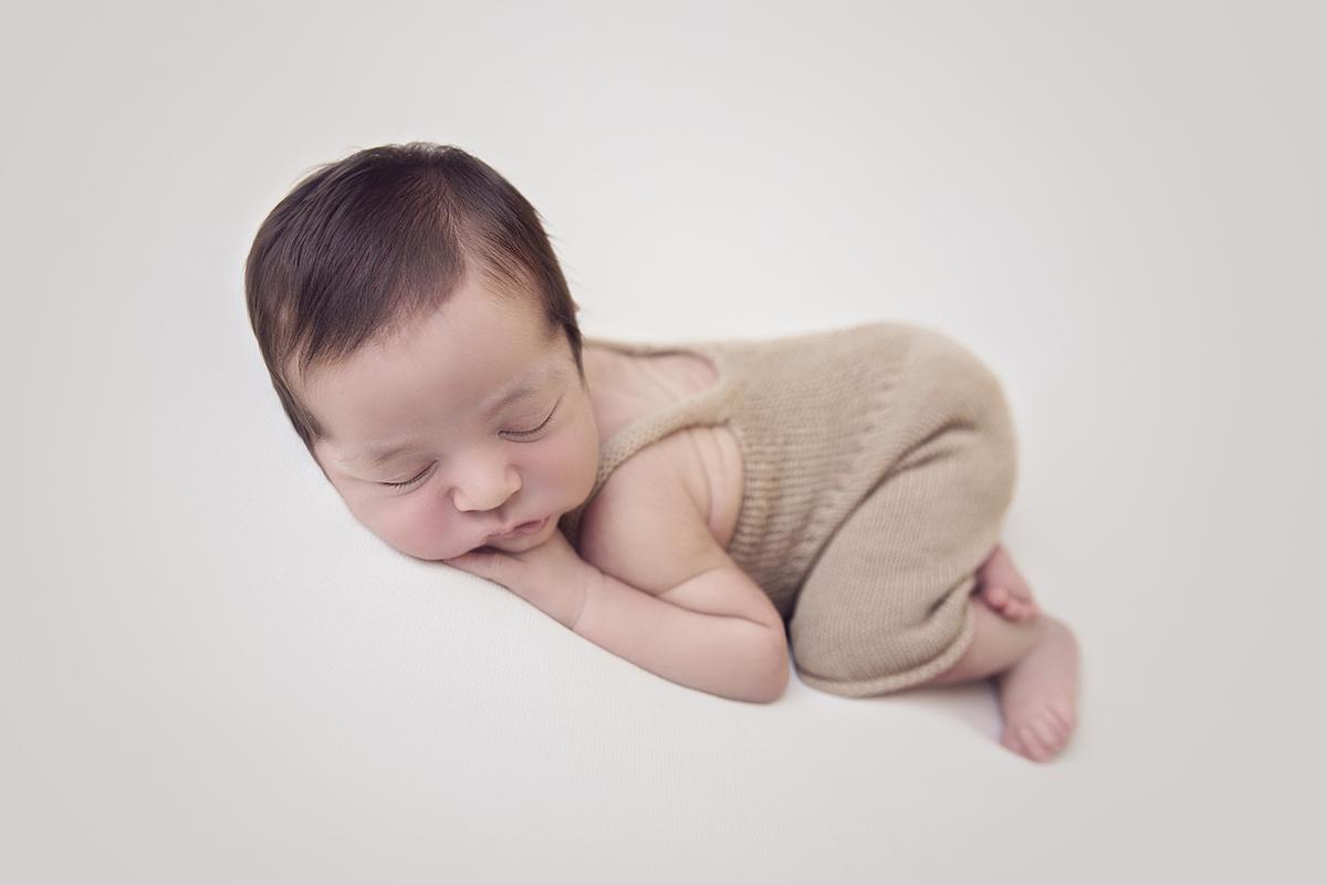 Ensaio Newborn menino em Brasilia na manta creme, com macacão