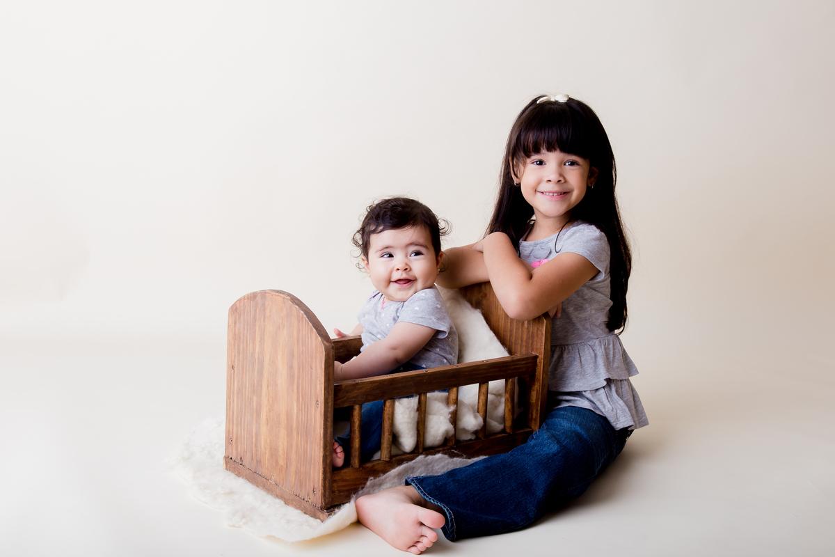 Ensaio de acompanhamento com irma mais velha, bebe de seis meses em ensaio primeiro ano