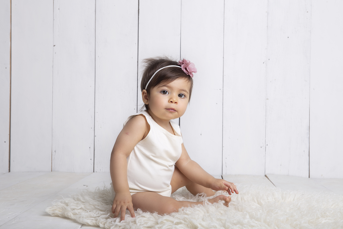 Bebê sentada em cenário branco, para seu ensaio de 9 meses, acompanhamento trimestral Brasilia DF