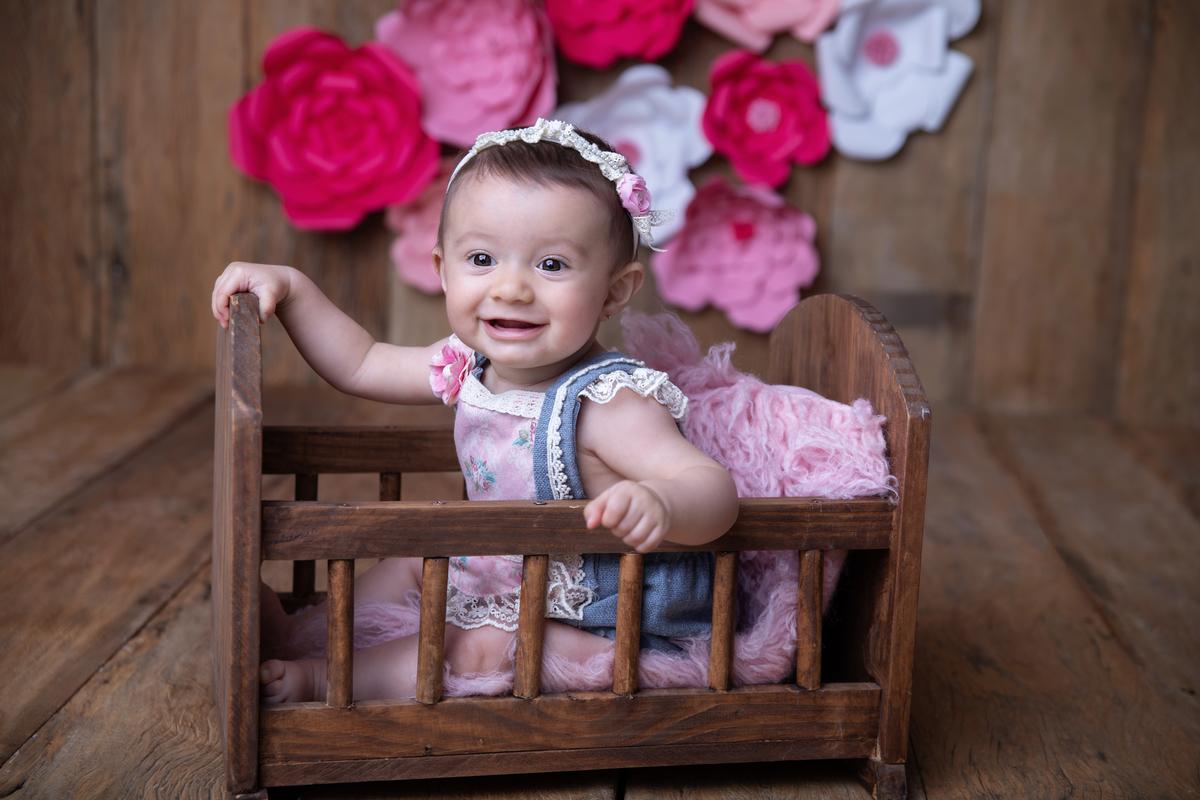 Bebê de seis meses no bercinho, rosa, acompanhamento trimestral Brasilia DF