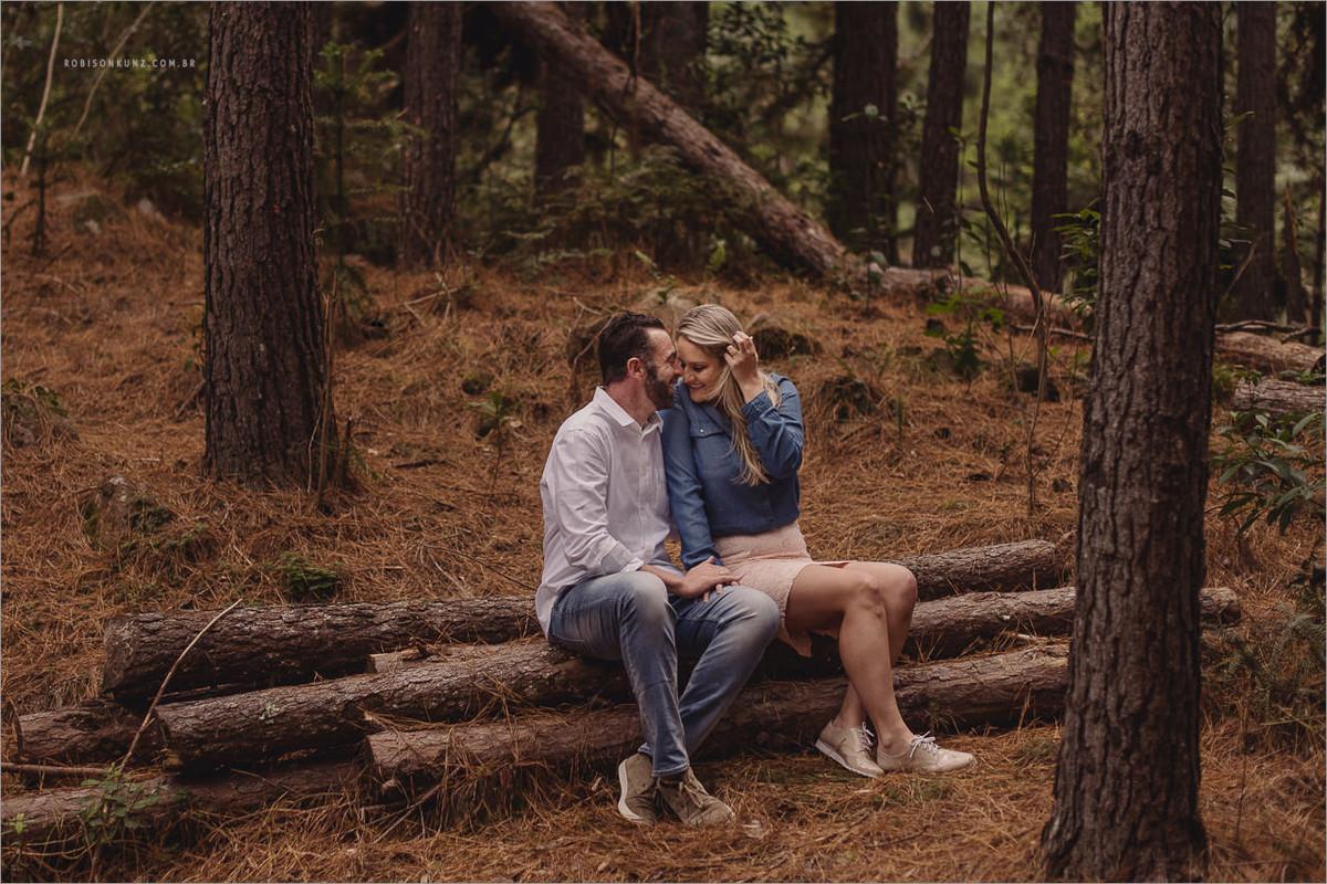 carina e eric fotografando no meio de uma floresta de pinos