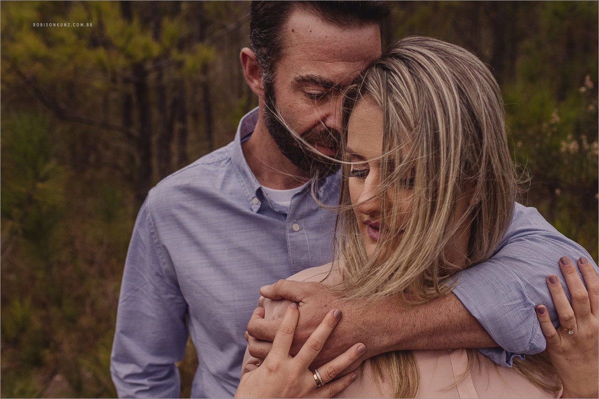 casal fotografado em um mato de pinos