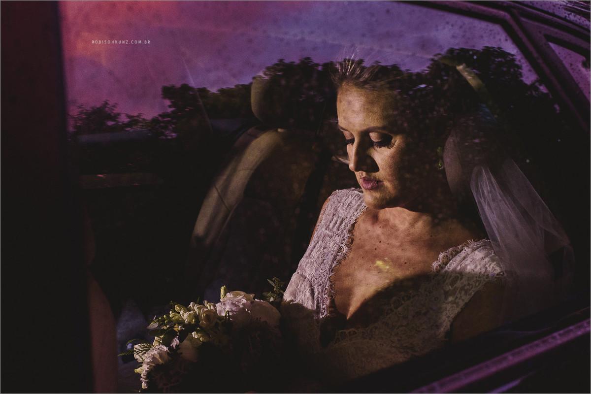 noiva esperando no carro com chuva