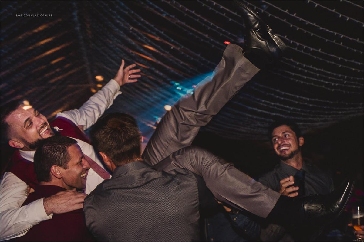 padrinhos jogando o noivo para cima
