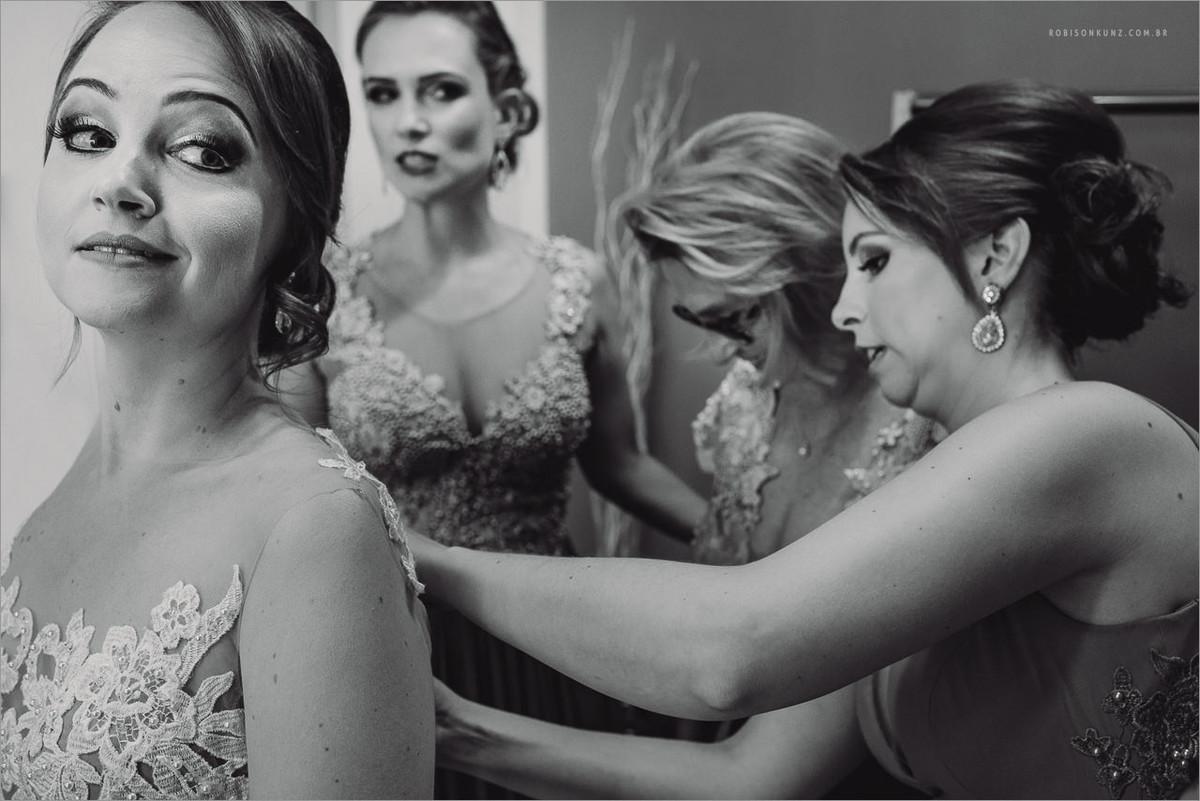 mae e irmãs vestindo a noiva