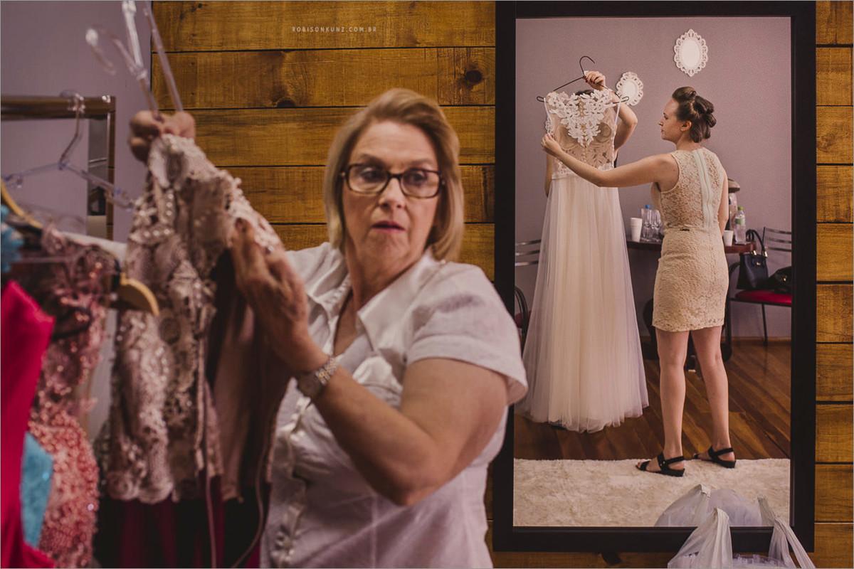 mae da noiva pegando os vestidos