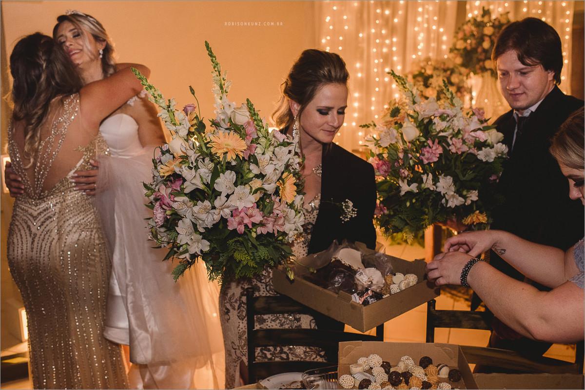 convidados levando flores e doces no final do casamento