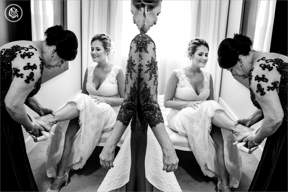 foto premiada com a mae e sogra vestindo a noiva