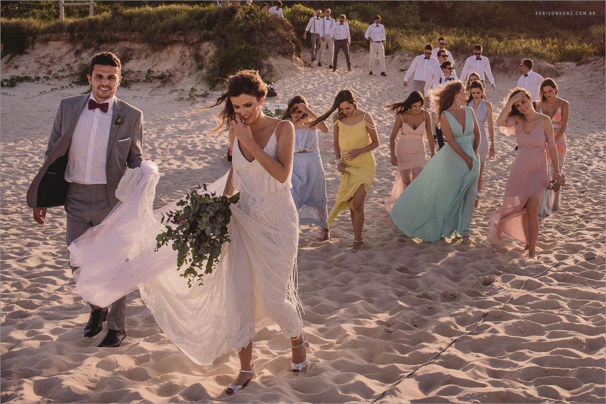noivos e padrinhos caminhando na areia