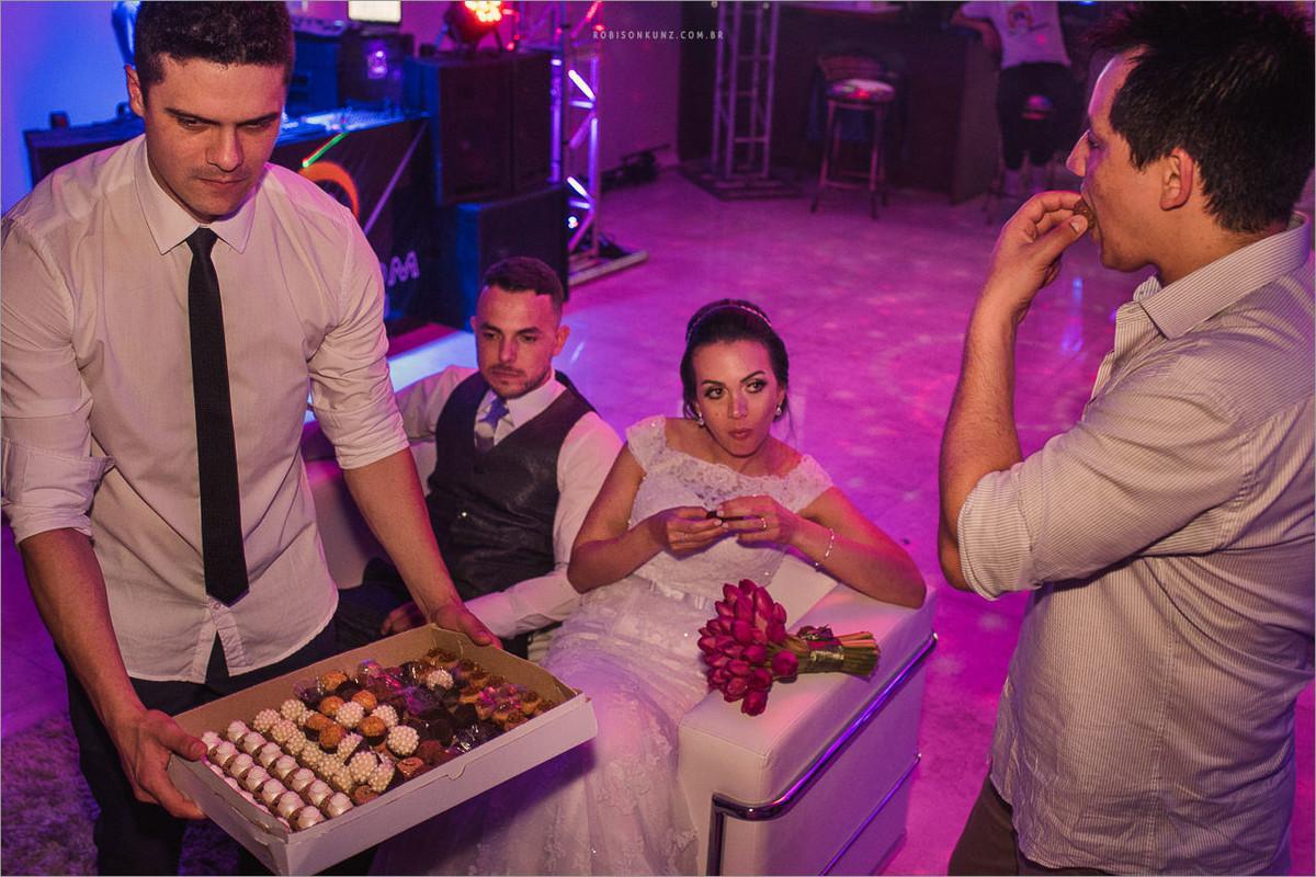 noivos e padrinhos comendo docinho no final do casamento