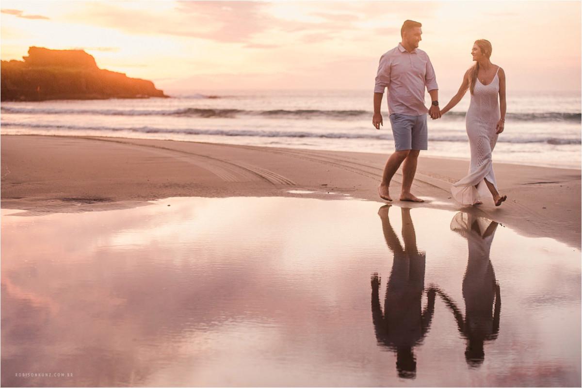 casal caminhando na beira mar no amanhecer