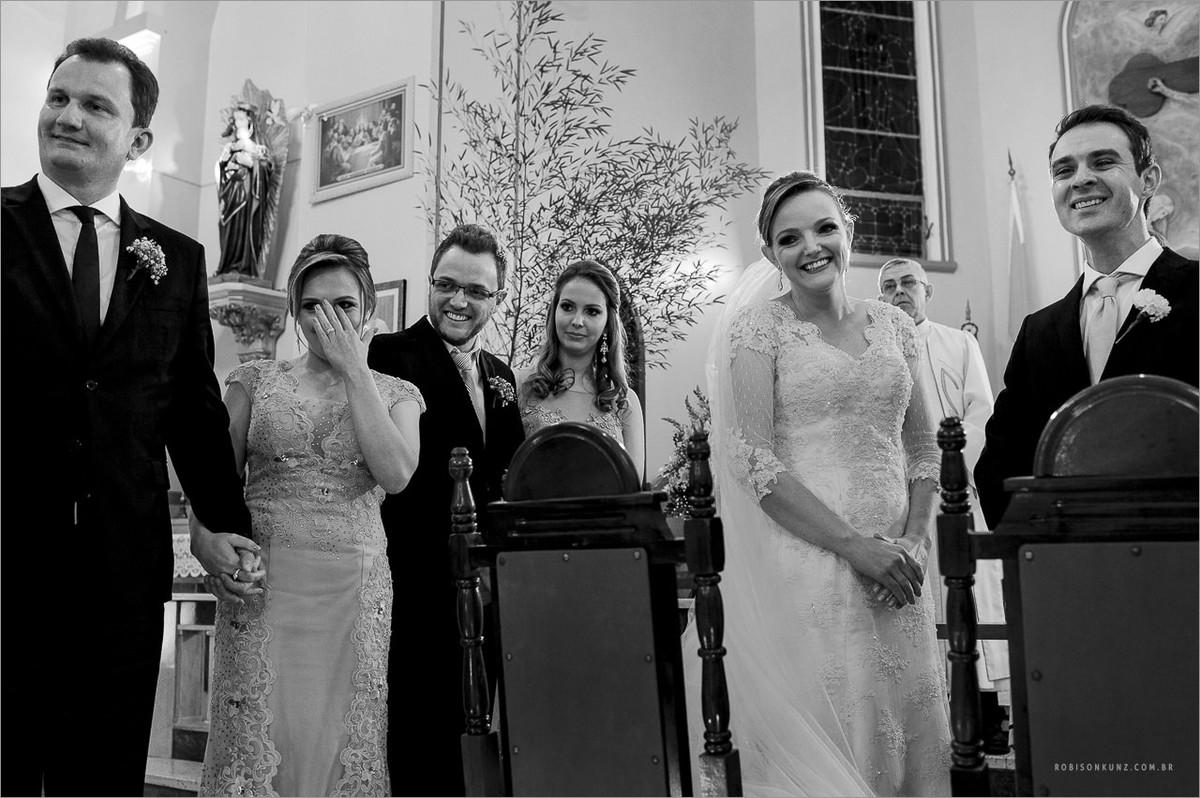 noivos e padrinhos emocionados ao verem as daminhas entrarem na cerimonia