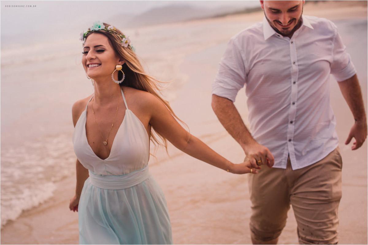 noivos correndo na beira da praia