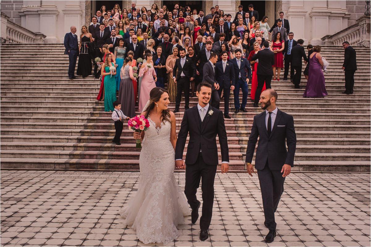 noivos e convidados na escadaria da igreja