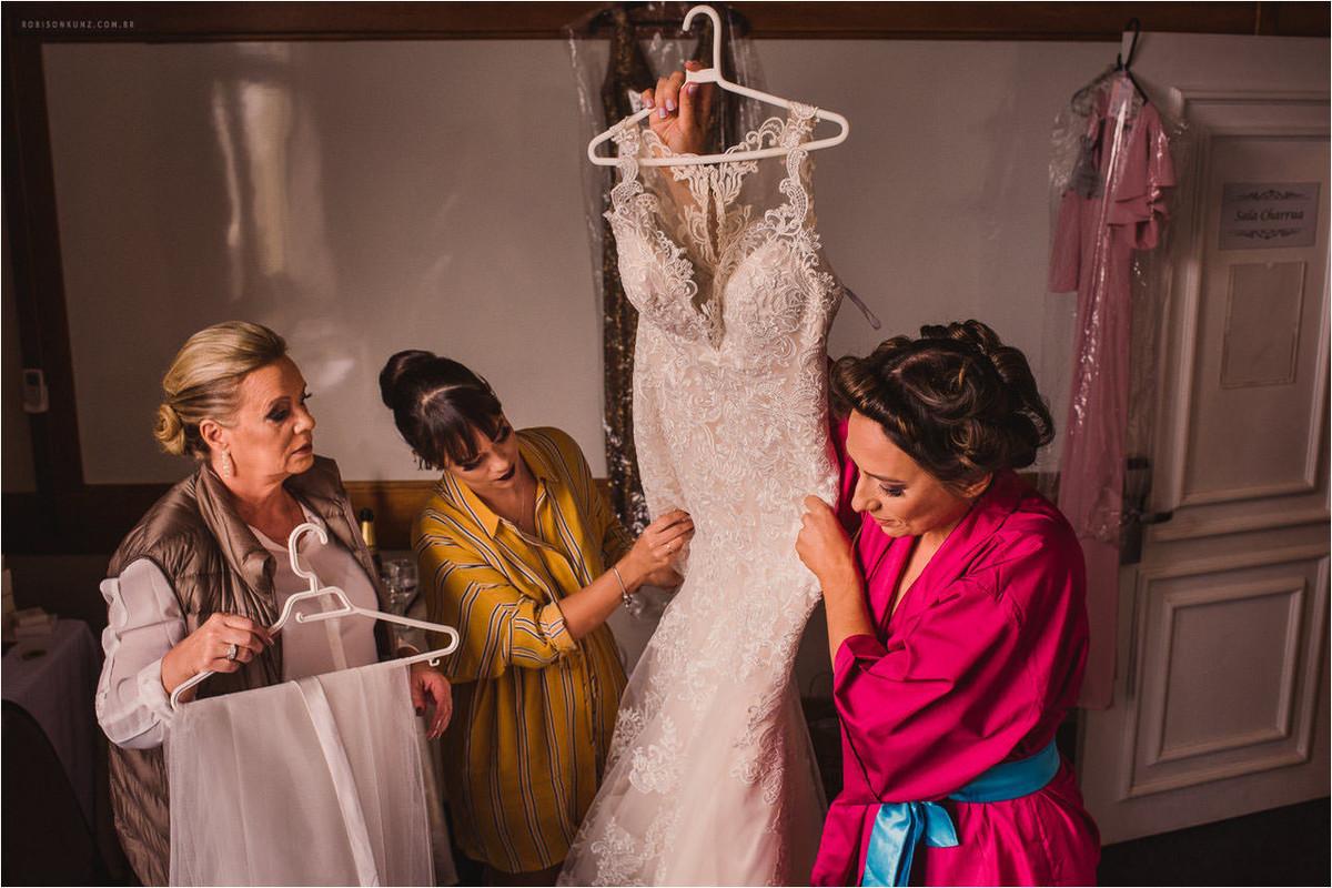 noiva e madrinha levando o vestido