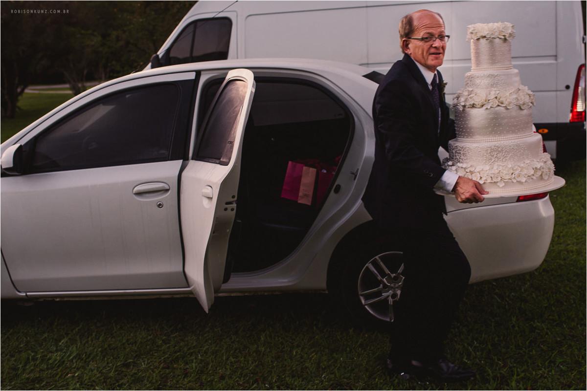 pai da noiva levando o bolo