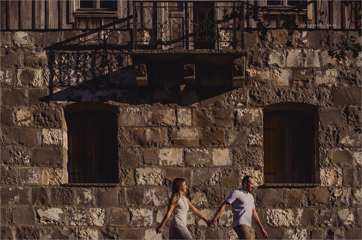 noivos correndo na frente de uma casa antiga