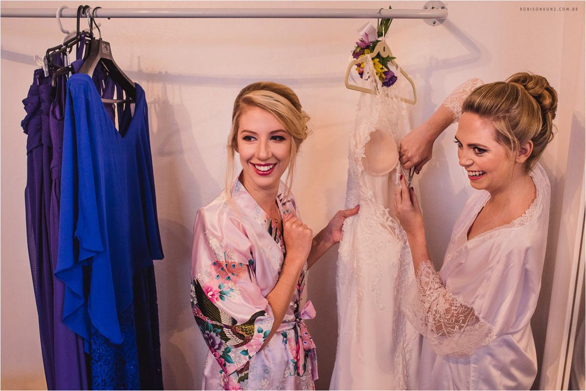 noiva e madrinha costurando o vestido