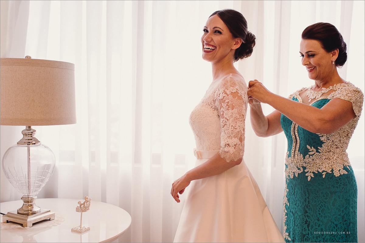 mae ajudando a colocar o vestido na noiva