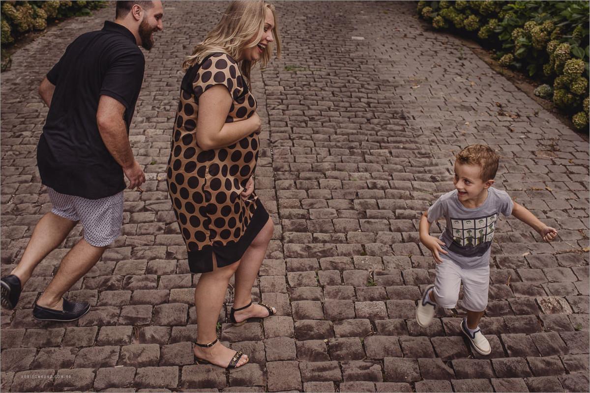 pai e filho correndo ao redor da mãe