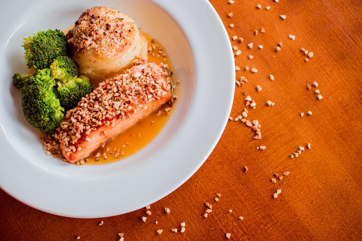 Salmão grelhado em crosta de castanha de caju, mil folhas de batata e molho de laranja com gengibre.