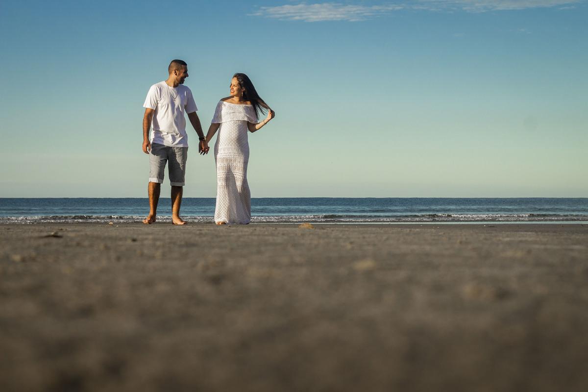 Pai e mãe de mãos dadas em ensaio gestante, na praia