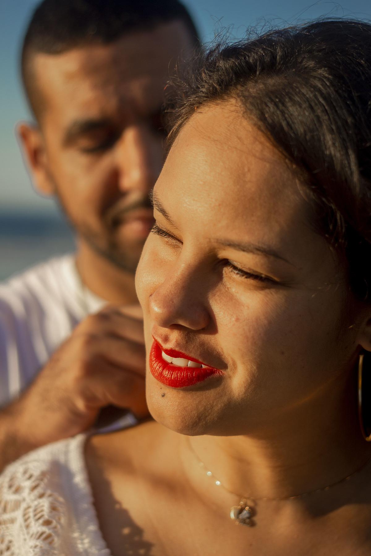 Pai acaricia mãe, em sessão de fotos de gestante na praia de boracéia