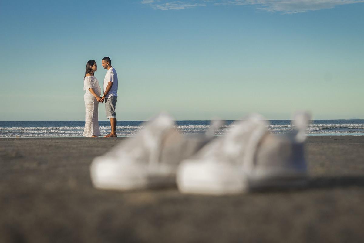 Pai e mãe , com sapatinhos do bebê, em um ensaio gestante na praia de Boracéia
