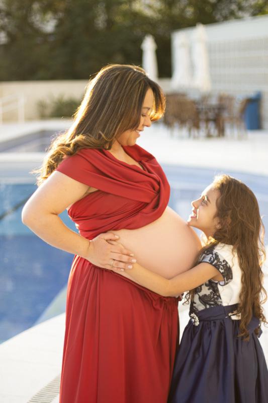 Ensaio gestante com vestido vermelho em apartamento com piscina , junto com a pequena irmã